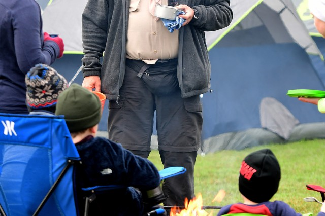 An Eagle Scout talks with some young Scouts gathered around a fire early Saturday morning as they try to stay warm. Temperatures dropped during the weekend Oct. 12-14, 2018, providing a cold backdrop to the Patriot Games.