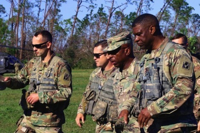 The Adjutant General of Florida, Maj. Gen. Michael C. Calhoun, briefs Lt. Col. Jason Hunt, commander, 1-153rd CAV and Command Sgt. Maj. Virgil Robinson, 53rd IBCT in Mexico Beach, Florida, following the aftermath of Hurricane Michael, Oct. 12, 2018. Calhoun, along with Florida Governor Rick Scott, flew to Mexico Beach to meet with local residents and to survey the damage from Hurricane Michael.