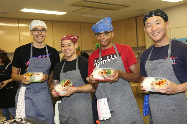 From left to right, Spc. Stephen Thompson, assigned to the U.S. Army Japan Band; Spc. Germaine Goodall and Sgt. William Birdsall, both assigned to the Military Police Battalion Japan; and Spc. Scott Gleason, assigned to the USARJ Band, show off the bento lunch boxes they made during a bilateral Japanese cooking class Oct. 13 at the Zama Health Center near Camp Zama.