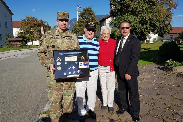 Master Sgt. Antonio Gonzalez, Provost Sergeant, and Mr. Richard Camacho, Physical Security manager, present a memorabilia box to Richard Bade, second from left, accompanied by his wife Wilma, on Sheridan Kaserne, Oct. 1, 2018.