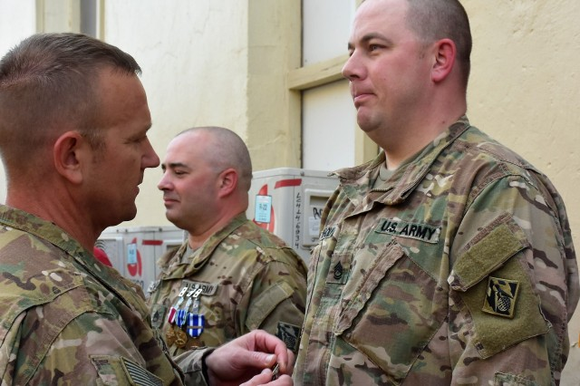 Sgt. 1st Class Jonathan Lindholm, a Prime Power contracting officer technical representative, was awarded the NATO Medal and Meritorious Service Medal for his service to the Area Support Group Afghanistan (ASG-A) during the command's Sept. 30 hail and farewell. The awards were presented by (left) ASG Commander Col. Jacob Peterson.