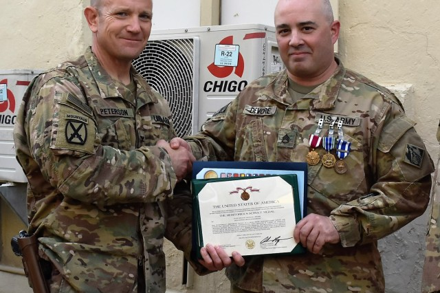 (From right) Staff Sgt. Douglas DeVore Jr., a Prime Power contracting officer technical representative, was awarded the NATO Medal, Army Achievement Medal and Meritorious Service Medal for his service to the Area Support Group Afghanistan (ASG-A) during the command's Sept. 30 hail and farewell. The awards were presented by ASG Commander Col. Jacob Peterson.
