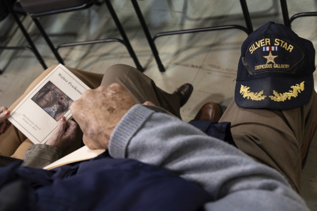 "A hat, with the words ""Silver Star"" embroidered on it, sits on an audience member's knee during Walter Pruiksma's Order of the Marechaussee award ceremony, Oct. 13, 2018, Mannasquan, N.J."