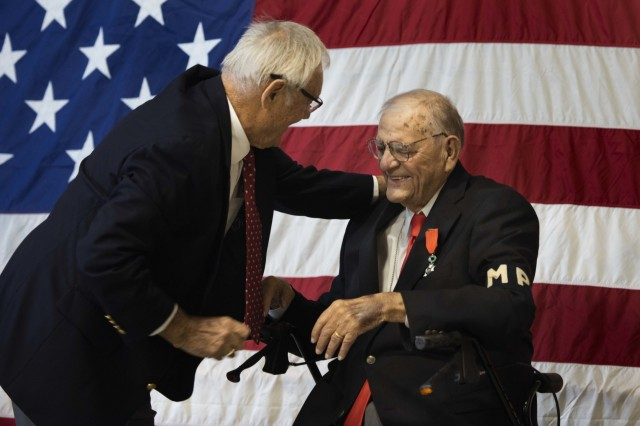 Al Schobel bends down to embrace Walter Pruiksma prior to Pruiksma receiving the Order of the Marechaussee in Silver at an award ceremony, Oct. 13, 2018, Mannasquan, N.J.