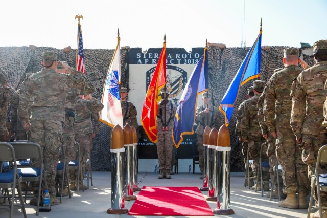KANDAHAR, AIRFIELD, Afghanistan -U.S. Sailors, Airmen, Soldiers, and Marines salute the nations colors, Oct. 14, 2018, during a transfer of authority ceremony in Kandahar Airfield, Afghanistan. The ceremony bid farewell to the U.S. Navy's Sierra rotation and welcomed Tango rotation to Kandahar Airfield and the NATO Role III Multinational Medical Unit. (U.S. Army photo by Staff Sgt. Neysa Canfield)