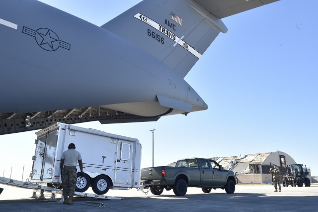 821st Contingency Response Group Airmen offload their mobile command and control trailer from a Travis Air Force Base C-17 Globemaster III, at Tyndall Air Force Base, Florida, Oct. 12, 2018. The mobility Airmen of this contingency response team deployed to assess damage and establish conditions for the re-initiation of airflow, bringing much needed equipment, supplies and personnel for the rebuilding of the base in the aftermath of Hurricane Michael. AMC equipment and personnel stand by across the nation to provide even more support upon request. (U.S. Air Force photo by Tech. Sgt. Liliana Moreno)