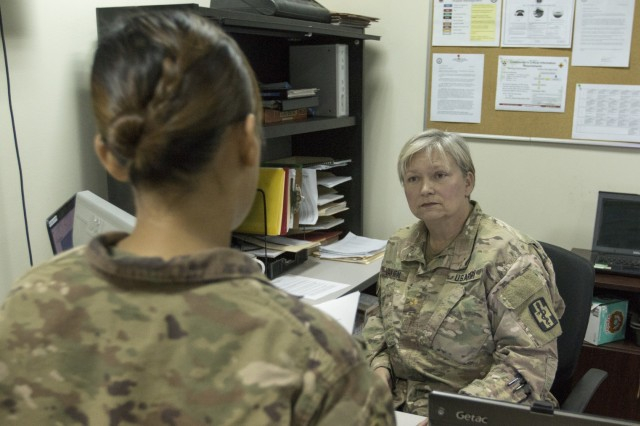U.S. Army Maj. Lisa Van Horn, the chief of patient administration at the 452nd Combat Support Hospital, listens to questions about hospital procedures from Spc. Rhea Peden, a patient administration specialist, at Camp Arifjan, Kuwait, Oct. 3, 2018.