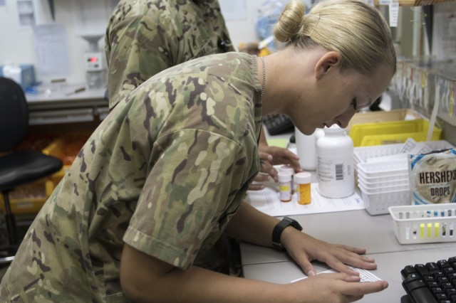 U.S. Army Pvt. 1st Class Jenna Van Horn, a pharmacy specialist with the 452nd Combat Support Hospital, prepares a prescription for a patient at Camp Arifjan, Kuwait, Oct. 3, 2018.