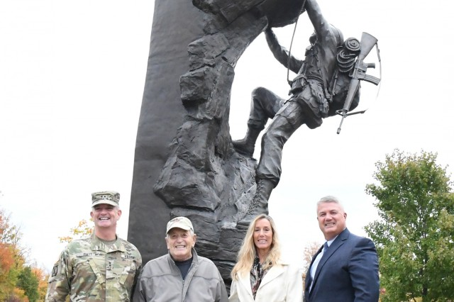Maj. Gen. Walter E. Piatt, 10th Mountain Division (LI) and Fort Drum commanding general, Robert Huni, Mary Ryan and Eric Wagenaar, deputy garrison commander, stand for a photo in front of the Military Mountaineer Monument in Memorial Park on Oct. 17 at Fort Drum, New York. Ryan and her father were invited to Fort Drum after she wrote about her experience running the Memorial to Monument Run in September. (Photo by Mike Strasser, Fort Drum Garrison Public Affairs)
