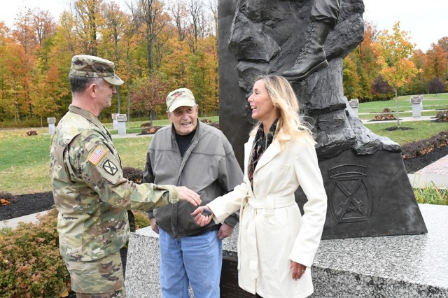 Maj. Gen. Walter E. Piatt, 10th Mountain Division (LI) and Fort Drum commanding general, presents a commander's coin to Robert Huni and his daughter Mary Ryan, during their visit Oct. 17 at Fort Drum, New York. Ryan, a North Syracuse resident and Syracuse Team Red, White and Blue member, ran the inaugural Memorial to Monument Run from Fort Drum to Watertown in September in honor of her father. (Photo by Mike Strasser, Fort Drum Garrison Public Affairs)