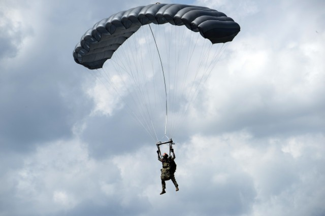 An operational jumper with combat equipment descending under the RA1 Double Bag Static Line system.