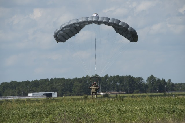 An operational jumper with combat equipment descends under the RA1 Double Bag Static Line system.