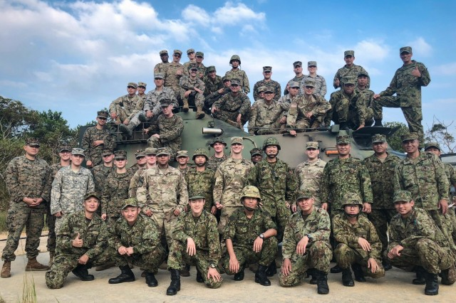 Participants from 1st Battalion, 1st Air Defense Artillery Regiment, 1st Marine Aircraft Wing, 18th Civil Engineer Squadron, and Japan Self Defense Force from the 15th Biological, Chemical Company, pose for a group photo on Combat Town, Camp Hansen, Oct. 10-11, 2018. The two-day CBRN exercise built upon previously joint/bilateral field training exercises designed to increase combat readiness and interoperability of U.S. forces and the Japan Self Defense Forces. (U.S. Photo by 1st Lt. Matthew B. Li)