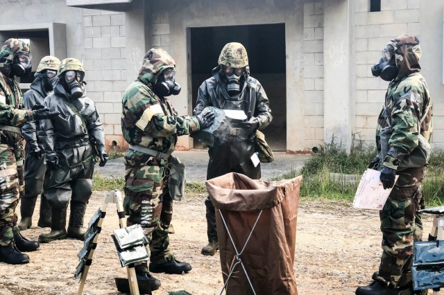 U.S. Airmen from the 18th Civil Engineer Squadron and Japan Self Defense Force service members from 15th Nuclear, Biological, Chemical Company, conduct detailed troop decontamination on Combat Town, Camp Hansen, Oct. 10, 2018. The training event is part of a two-day CBRN exercise built upon previously joint/bilateral field training exercises designed to increase combat readiness and interoperability of U.S. forces and the Japan Self Defense Forces. (U.S. Photo by 1st Lt. Matthew B. Li)
