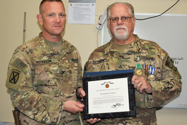 (Right) Department of Defense Expeditionary Civilian (DOD-EC) Jeffrey Olson was awarded the NATO Medal, Global War on Terrorism Medal and Commander's Award for Civilian Service for his service to the Area Support Group Afghanistan mission at ASG-A's Forward Operating Base (FOB) Fenty in Jalalabad Oct. 11, 2018. The awards were presented by (left) ASG Commander Col. Jacob Peterson.