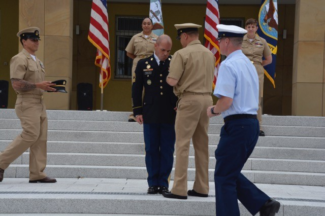 Master Chief Joel Steinbach is joined by Senior Chief Petty Officer Richard Whitney to ceremoniously pin the Chief's Anchors on Army Master Sgt. Jacob Huckleby. Chief Jay Vazquez approaches to put on Huckleby's cover.