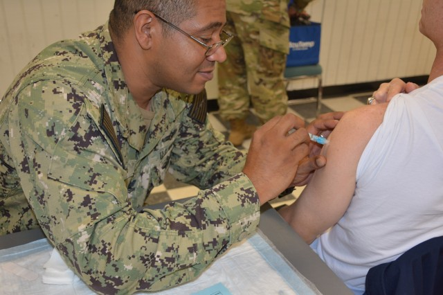 Navy corpsman from Kimbrough SRP team provides flu shots at the flu fair.