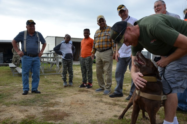 FORT BENNING, Ga. (Oct. 18, 2018) - Jegs, a military working dog, meets former members of the 60th Infantry Platoon (Scout Dog) and their Family members. The six Vietnam War veterans visited Fort Benning Oct. 17 after almost 50 years to see how military working dogs were employed today. (U.S. Army photo by Bryan Gatchell, Maneuver Center of Excellence, Fort Benning Public Affairs)