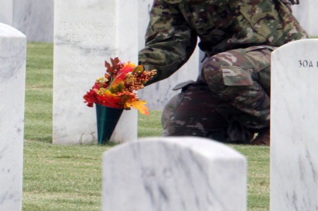 A trainee carefully scrubs a headstone at the Fort Sill National Cemetery in Elgin, Okla.