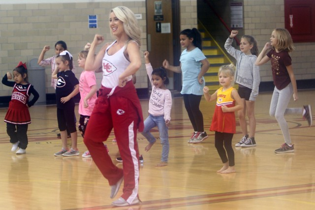 Kansas City Chiefs cheerleader Caroline leads budding cheerleaders between the ages of 5 and 18 in a series of stretching exercises during a cheerleading clinic Oct. 13, 2018, at Honeycutt Fitness Center.