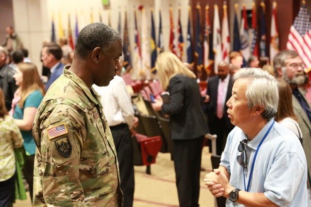 Maj. Gen. Cedric T. Wins, U.S. Army Research, Development, and Engineering Command commanding general, speaks with Myung Rhee, an employee in the Aviation Engineering Directorate at the RDECOM Aviation and Missile Center, during safety day.