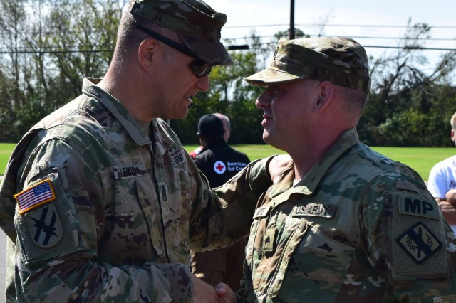 Command Sgt. Major Shawn Lewis, senior enlisted advisor to the Ga. Army National Guard congratulates Sgt. Blake Mote of the Kennesaw-based 190th Military Police Company for his actions on Oct. 17, 2018 when he assisted firefighters in suppressing a house fire in Seminole County, Ga. In his civilian capacity, Mote, is a firefighter and advanced emergency management technician with the Clayton County Fire and Emergency Management Services. He and his unit have conducted relief operations in Dougherty and Seminole County, Ga. since October 11.