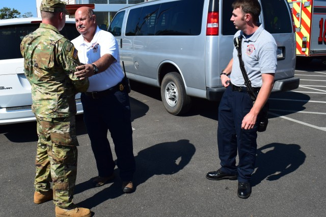 Dean King, Fire Chief of the Donalsonville Fire and Emergency Medical Services and Lieutenant Michael Smith thank Sgt. Blake Mote of the Georgia Army National Guard's 190th Military Police Company for his actions on Oct. 17, 2018 when he assisted firefighters in suppressing a house fire in Seminole County, Ga. In his civilian capacity, Mote is a firefighter and advanced emergency management technician with the Clayton County Fire and Emergency Management Services. He and his unit have conducted relief operations in Dougherty and Seminole County, Ga. since October 11.