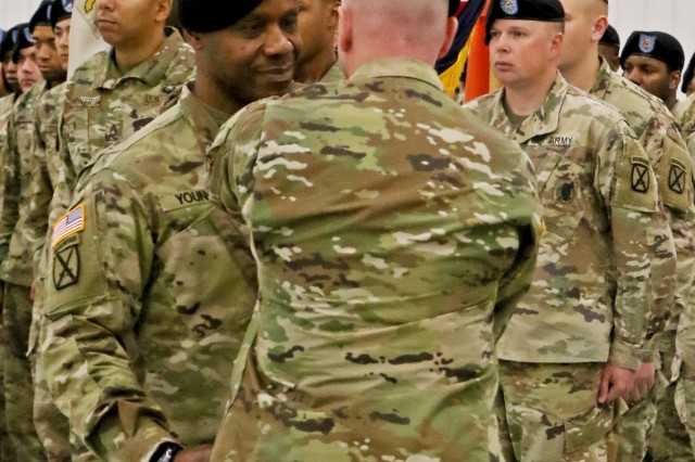 Incoming Command Sgt. Major Roy L. Young accepts the brigade colors from Brigade Commander Matthew Bresko during a Change of Responsibility ceremony at Fort Drum's Wheeler-Sack Army Airfield on Friday, October 19. Young has previously served in the 10th Mountain Division Sustainment Brigade, and now re-joins it as the senior non-commissioned officer.