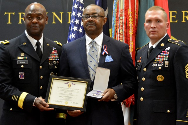 Perry W. James IV, the grandson of World War I veteran Sgt. Perry Loyd, receives his ancestor's Purple Heart from Fort Jackson commander, Brig. Gen. Milford 'Beags' Beagle Jr., and post Command Sergeant Major Jerimiah E. Gan during a ceremony Oct. 13, 2018 at Fort Jackson.