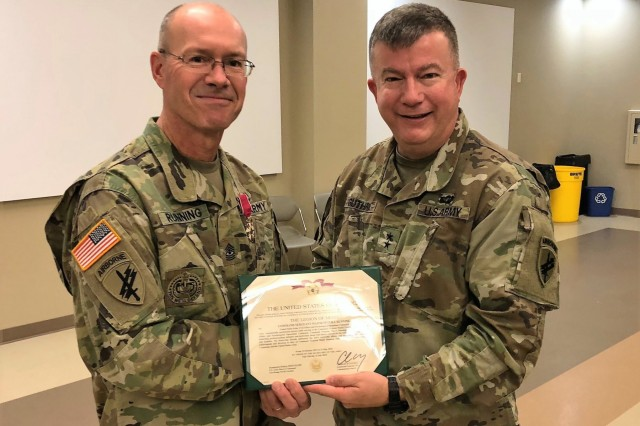 Sgt. Maj. Peter Running, left, the former command sergeant major of United States Army Civil Affairs and Psychological Operations Command (Airborne), poses with Maj. Gen. Darrell Guthrie, USACAPOC(A) commanding general, ater being awarded a legion of Merit for his time as senior enlisted leader Saturday, October 20, 2018 at the USACAPOC(A) headquarters on Fort Bragg. Running left his position at USACAPOC(A) to become the senior enlisted advisor for Lt. Gen. Charles Luckey's Commander's Action Group at the Office of the Chief of the Army Reserve in Washington, D.C. (Photo by Lt. Col. Jefferson Wolfe, USACAPOC(A) public affairs officer)