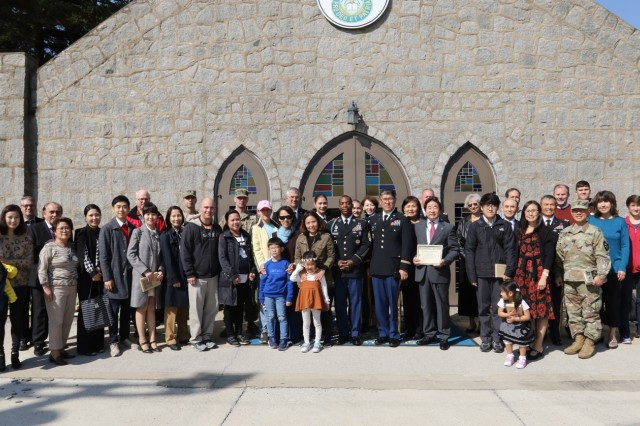 CAMP RED CLOUD, Republic of Korea -- The Camp Red Cloud community, together with members from U.S. Army Garrison Yongsan, USAG Camp Humphreys, and 2nd Infantry Division/ROK-U.S. Combined Division, pose in front of the Warrior Chapel, signifying the final closing of the chapel doors following the decommissioning ceremony Oct. 21. The functions and community services of the Warrior Chapel have relocated to U.S. Army Garrison Camp Humphreys to continue serving the community members as it has for the past 66 years. The 2ID/RUCD is in the process of returning Camp Red Cloud to the Korean government as a part of the transformation plan.