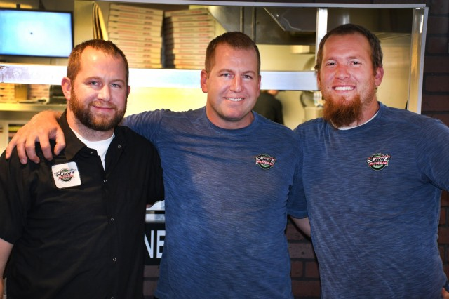 Idaho Army National Guard Sgt. Brian Padigimus, center, poses for a photo with his brother, Geoff Padigimus, and friend, Tim Wright, at Lucy's New York Style Pizzera in Pocatello, Idaho, Sept. 19, 2018. Padigimus, an infantryman assigned to the 116th Cavalry Brigade Combat Team, started the restaurant with Wright in 2009. A short time later, Geoff joined the ownership group and today the trio owns four restaurants in Idaho and Utah.