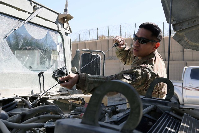 Sgt. Roque Torres, 1st Security Force Assistance Brigade, checks the oil on an Afghan Humvee as part of a video being shot at Forward Operating Base Lightning, Afghanistan, Oct. 12. (Photo by Jon Micheal Connor, Army Public Affairs)