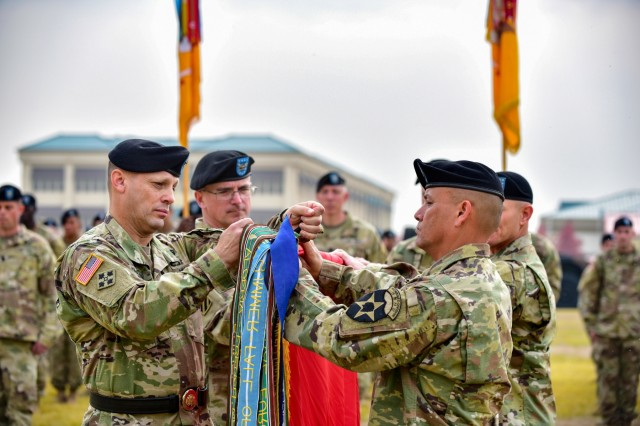 CAMP HUMPHREYS, Republic of Korea - Maj. Gen. Scott McKean, a San Jose, California native, commander, 2nd Infantry Division/ROK-U.S. Combined Division, and Command Sgt. Maj. Phil K. Barretto, the 2ID/RUCD CSM, and Aiea, Hawaii native, place a streamer on the 1st Armored Brigade Combat Team, 3rd Infantry Division, brigade colors during a transfer of authority ceremony with 3rd ABCT, 1st Armored Division at Camp Humphreys, October 22nd. 3rd ABCT will serve as the rotational brigade under the 2nd Infantry Division/ROK-U.S. Combined Division. This marks the first time that 1st AD Soldiers have deployed to Korea. (U.S. Army Photo by Mr. Pak, Chin U., 2ID/RUCD Public Affairs)