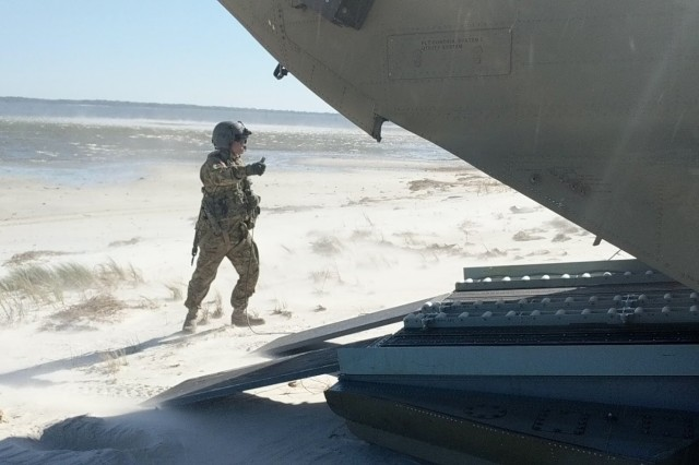 A CH-47 Chinook crewmember from the New York Army National Guard's Company B, 3rd Battalion, 126th Aviation assists with the offload of rescue personnel and vehicles October 13 near Alligator Point, a barrier island off Apalachicola Bay, Florida following the impact of Hurricane Michael. The New York Army National Guard crews deployed 11 personnel and two aircraft to support the Florida Guard's 1st Battalion, 111th Aviation Task Force. Crews flew for three days, transporting 32, 240 pounds of cargo before returning to their flight facility in Rochester, N.Y. October 17.
