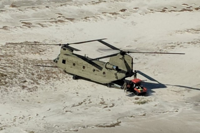 A New York Army National Guard CH-47 Chinook helicopter transports search and rescue personnel and their all-terrain vehicles to St. Teresa, along the shoreline of the Florida panhandle October 12, 2018. The New York Army National Guard Soldiers deployed two Chinooks and two UH-60 Black Hawk helicopters along with 25 crewmembers to Tallahassee, Florida to assist with response and recovery efforts for the Florida National Guard following the impact of Hurricane Michael.