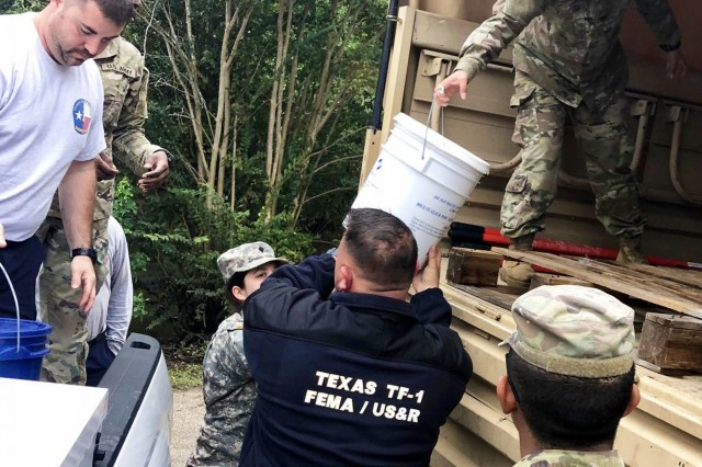 Texas National Guardsmen alongside members of Texas Task Force 1 unload supplies to distribute to flood-affected neighborhoods near Huntsville, Texas, Oct. 20, 2018. Soldiers with the 949th Brigade Support Battalion based in Dallas - Fort Worth were mobilized Oct. 17, 2018, to assist with flood relief efforts in affected neighborhoods across Texas.