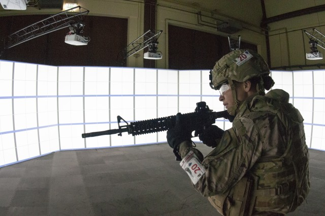 Spc. Olivia Silver, assigned to 1st Armored Brigade Combat Team, 1st Cavalry Division scans for targets at the Gunfighter Gymnasium shooting simulation drill during the 2018 European Best Warrior Competition held at the 7th Army Training Command's Grafenwoehr Training Area, Germany, Aug. 13, 2018. Competition winners will be announced for this year's top junior officer, noncommissioned officer and Soldier during a concluding ceremony scheduled for Aug. 17, 2018.