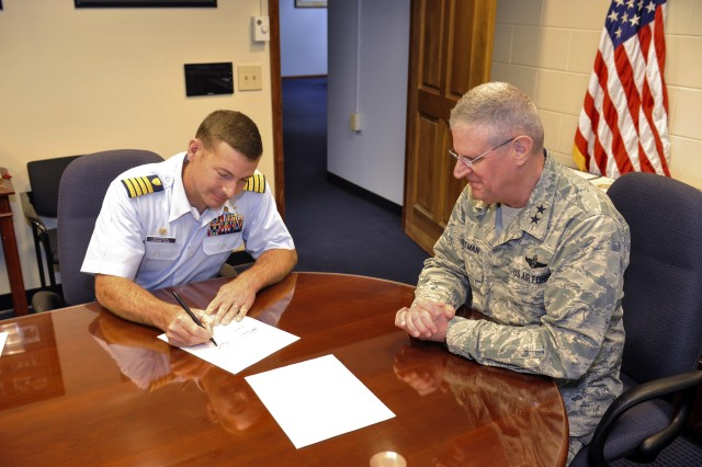 Maj. Gen. Mark E. Bartman (right), Ohio adjutant general, watches Capt. Greg Rothrock, Coast Guard Research and Development Center commanding officer, sign a joint memorandum of understanding (MOU), Oct. 22 at Ohio National Guard Joint Force Headquarters in Columbus, Ohio. This is the first time the USCG RDC has signed an MOU with a state's National Guard, and will allow the ONG and USCG RDC to work together on cyber engagements.