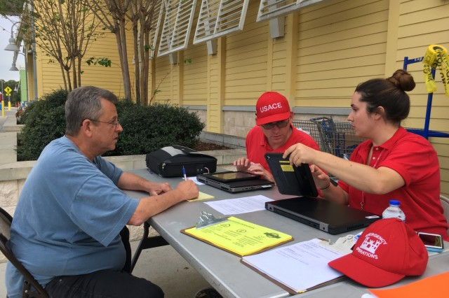 """David McFadden, U.S. Army Corps of Engineers, Little Rock District and Monica Chahary, New York District, assist a Panama City, Fla., resident sign up his home for free temporary roof repairs through Operation Blue Roof Monday Oct. 22, 2018. Operation Blue Roof program is a FEMA program being administered by the U.S. Army Corps of Engineers to provide temporary roof repairs to residents in Florida counties impacted by Hurricane Michael to help reduce further property damage until permanent repairs can be made.""""I used to work in the non-profit sector and I enjoy helping people, especially most in need like the ones here,"""" Chahary said about deploying to Florida as part of the larger Hurricane Michael response and helping people sign up for Operation Blue Roof. """"I enjoy working with people one on one and hearing their stories and helping them work through signing up and understanding the process."""""""