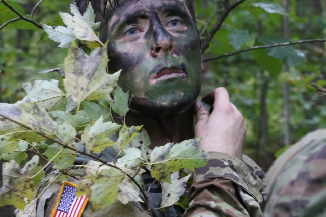 """A Cadet from Duke University applies camouflage at the """"Camouflage Yourself and Equipment"""" station during the 4th Brigade Ranger Challenge held at Fort Pickett, Va. Oct. 20."""