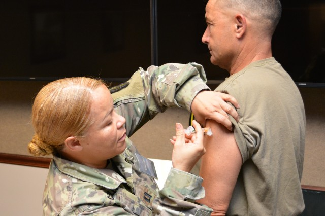 Capt. Mildred Castillo, chief of Preventative Medicine and Public Health at Lyster Army Health Clinic, administers the flu shot to Chief Warrant Officer of the Aviation Branch CW5 Joseph B. Roland at the U.S. Army Aviation Center of Excellence headquarters building Oct. 23.