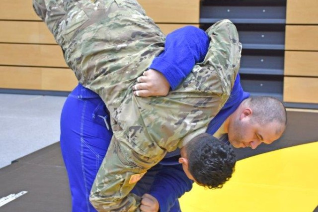 Rob Austin, with the Wiesbaden Brazilian Jiu Jitsu Club, demonstrates techniques with Specialist Ali Rebollo with the 60th Geospatial Planning Center during the Resiliency Fest Sept. 21 at the fitness center.
