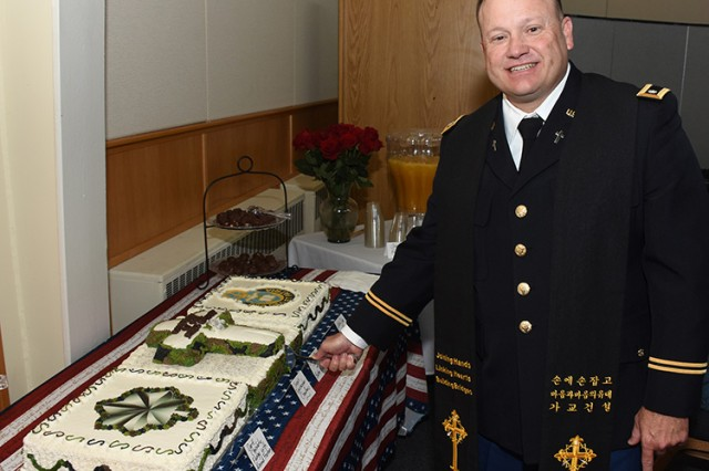 181001-A-BB276-025 Chaplain (Lt. Col.) James Lester stands beside a cake that Dugway Proving Ground, Utah, resident Suna Bridgman made to congratulate him for promotion to lieutenant colonel. The ceremony was Oct. 1, 2018 in the Dugway Hope Chapel. Photo by Al Vogel, Dugway Proving Ground Public Affairs.