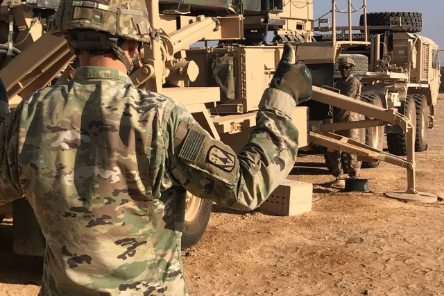 Spc. Bradlee Griffith, a launcher crew member, gives hand signals to Spc. Daivon Ballard during the C Battery, 3-2nd ADA Table VIII certification. Launcher crews are required to move and emplace their launchers in a timely fashion during the certification.