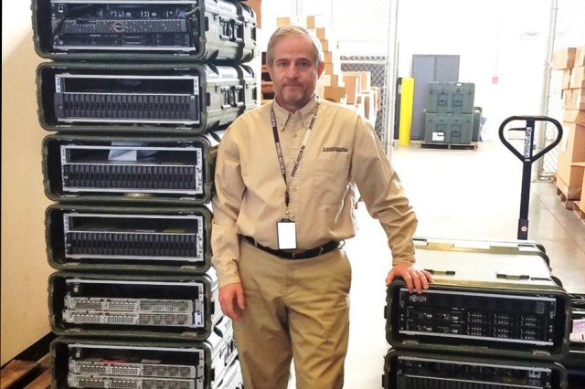 Rick St. Clair of Army Project Manager Mission Command stands between legacy Tactical Server Infrastructure (left) and the future TSI v2 at Aberdeen Proving Ground, Maryland.