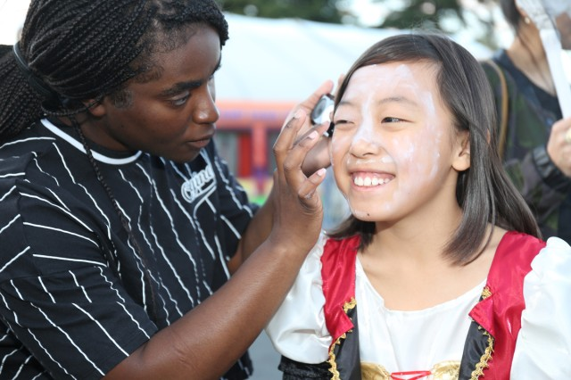 Private First Class Keturah Miller, assigned to 35th Combat Sustainment Support Battalion, paints Mina Harada's face during an annual Halloween trunk-or-treat event Oct. 24, 2018, on Sagamihara General Depot.