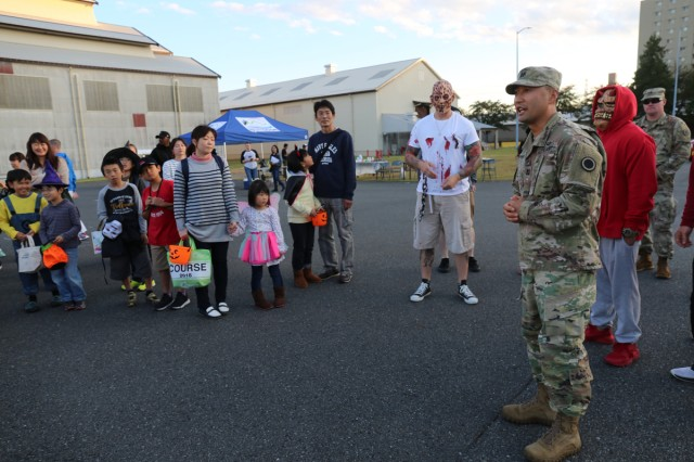 Captain Nathan Seaman, commander of 623rd Movement Control Team, 35th Combat Sustainment Support Battalion, welcomes local community members during an annual Halloween trunk-or-treat event Oct. 24, 2018, on Sagamihara General Depot.