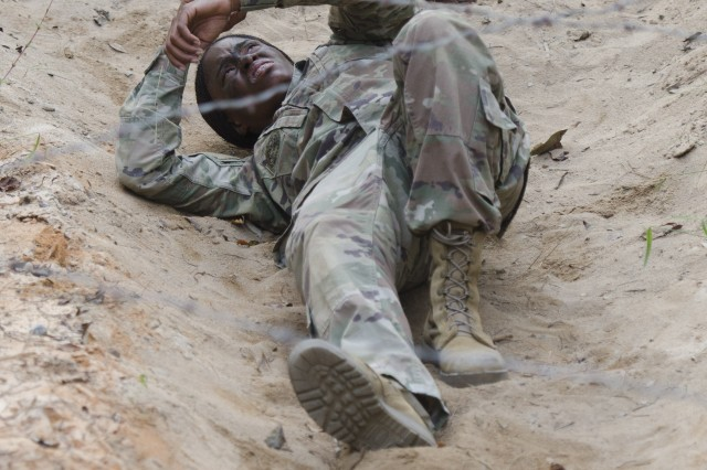 Staff Sgt. Nichole Danley, 1st Battalion, 61st Infantry Regiment carefully inches toward the end of the Low Wire obstacle during the Drill Sergeant/Non-commissioned Officer/Soldier of the year competition held on Fort Jackson, Oct 23 -27.