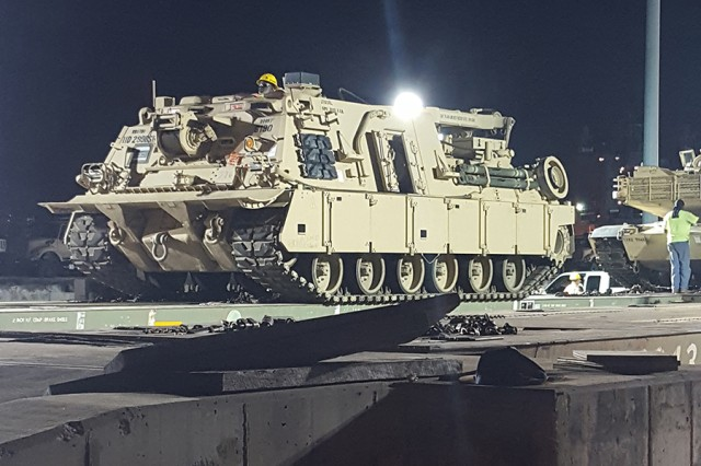A longshoreman carefully drives an M88 armored recovery vehicle off a rail car for staging at the Port of Beaumont, Texas, on Aug. 13, 2017.